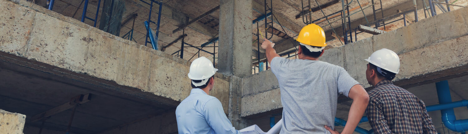 men in hard hats discuss construction for a business relocation